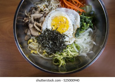 Korean Bibimbap Rice Bowl Topped with Egg and Vegetables Served in a Metal Bowl