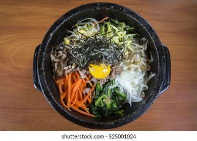 Korean Bibimbap Rice Bowl Topped with Egg and Vegetables Served in a Black Bowl