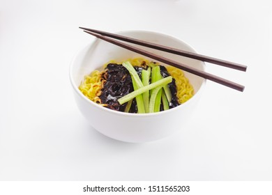 Korean Black bean noodle - jajangmyeon noodle with black sauce and vegetable in white bowl and chopsticks on white background