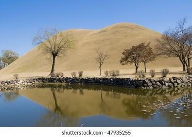 A Korean burial mound (Dolmen) from the ancient Silla kingdom, reflected in the calm waters of a pond in the foreground.
