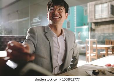 Korean businessman paying his restaurant bill with credit card. Asian businessman paying with contactless credit card at restaurant.