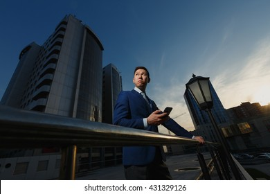 Korean businessman talking on phone in business district, on  background of skyscraper. Talking on phone, looking into distance, thinking takes an solution. Business style jacket, city and  building