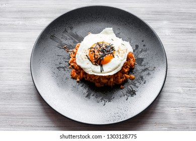 korean cuisine - above view of Kimchi bokkeum bap (fried rice with kimchi, beef and fried egg) on black plate on wooden board