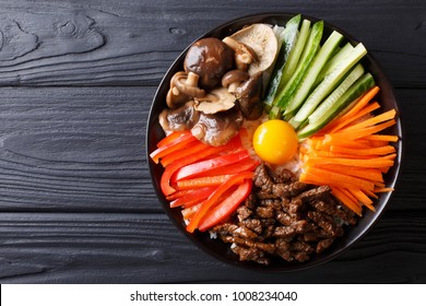 Korean cuisine: Bibimbap with beef, raw yolk, vegetables and rice on a plate. horizontal top view from above