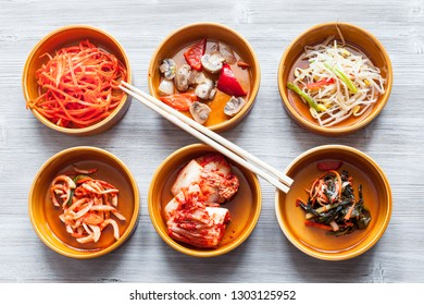 korean cuisine - chopsticks above various appetizers (Banchan or Panchan) in ceramic bowls on gray table