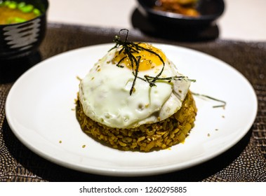 korean cuisine - Kimchi bokkeum bap (fried rice with kimchi, beef and fried egg) on white plate on brown leathed board in local restaurant