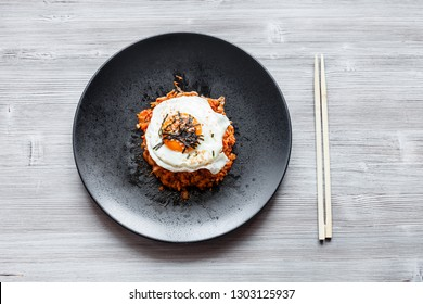 korean cuisine - top view of Kimchi bokkeum bap (fried rice with kimchi, beef and fried egg) on black plate and chopsticks on wooden board