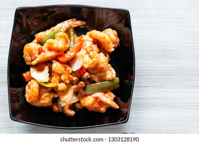 korean cuisine - top view of stir-fried Shrimps with cashew nuts and vegetables in sweet and sour sauce (Shrimps Combo) in black bowl on wooden table with copyspace