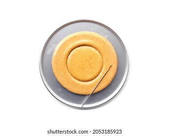 Korean Dalgona or Ppopgi honeycomb sugar candy with circle shape and needle in round tin tray on white background - Shutterstock ID 2053185923