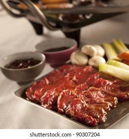 Korean dish bulgogi setup iwth meat, vegetables and grill