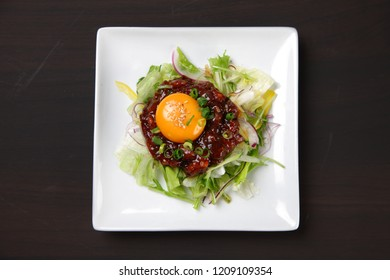 Korean dish of seasoned raw horse topped with an egg yolk