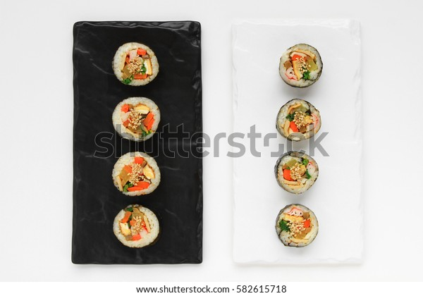 Korean dried Seaweed Rolls, gimbap. Made with carrot, eggs, kim, rice, salt, sesame oil, vinegar, sesame seeds, yellow radish, carrots, ham, spinach, fish cakes, burdock, eggs, rice, crab meat.