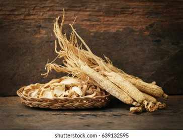 Korean dry ginseng roots on wood background.