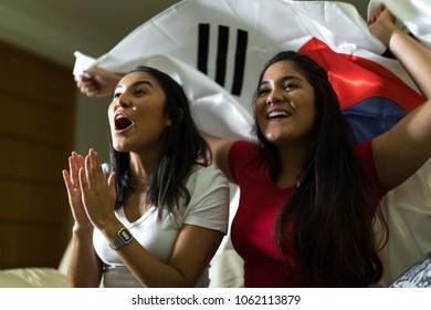 Korean fan celebrating during soccer match at home