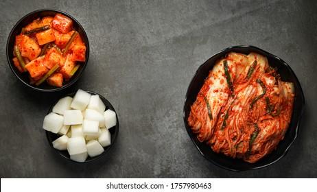 Korean food, Cabbage kimchi and Radish kimchi and Pickled radish in black bowl set on dark background.
