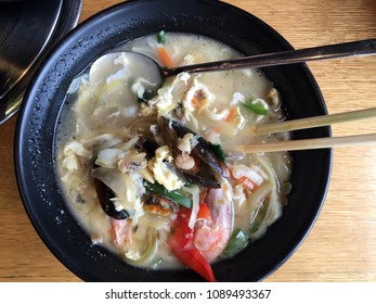 Korean Food - Spicy seafood noodle. Korean Soup Food. Delicious seafood noodle soup with chicken stew and shellfish, oysters, octopus, different fish  in a hot pot. korean food background