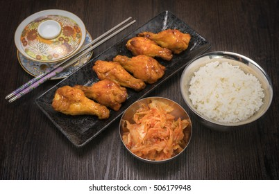 Korean fried chicken with sauce ,Korean style deep fried chicken wings spicy barbecue sauce with rice and kimchi.