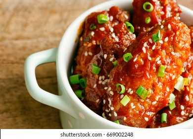Korean fried chicken wings or barbecue sprinkled with sesame and scallion on ceramic bowl so delicious,moist and spicy. Goodness food  fried chicken wings in Korean style on wood table with copy space