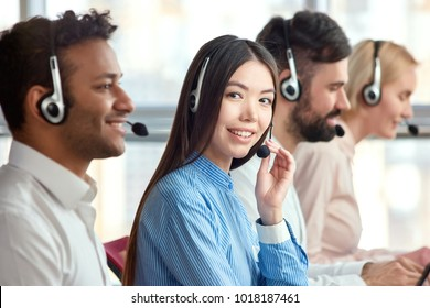 Korean girl in call center with colleagues. Side view of line of call centre employees with focused smiling asian girl smiling with manager.