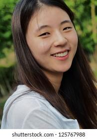 Korean girl smiling showing teeth.