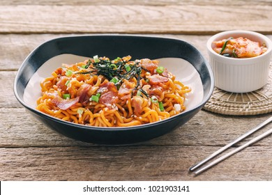 Korean hot and spicy instant noodle in black and white bowl topped with bacon, sesame, seaweed and chopped scallion served with kimchi on wood table in side view. Homemade delicious asian food concept