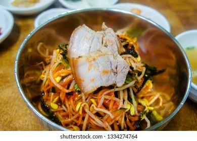 Korean Jeju Island Food, which is called bibim gogi guksu. Noodle Soup with Pork, green onion, laver and gochujang.