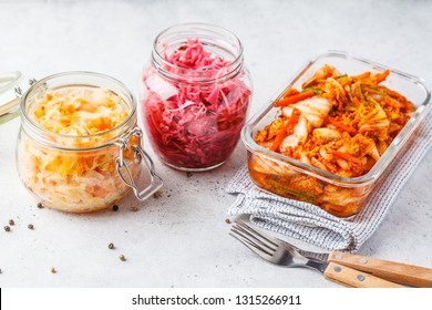 Korean kimchi cabbage, beet sauerkraut and sauerkraut in glass jars, white background. Probiotics food concept.