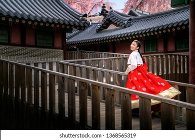 Korean lady in hanbok dress costume runing  in an ancient Gyeongbokgung palace in Seoul city, South Korea, this image can use for travel, and tourist Seoul.