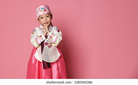 Korean little baby girl in traditional silk dress for new year celebration on pink background with hands in pray sign