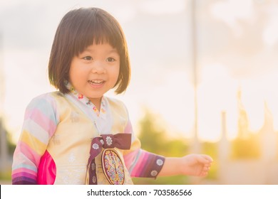 Korean little girl wearing a Traditional Hanbok or korean traditionnal costume in nature on sunset time.