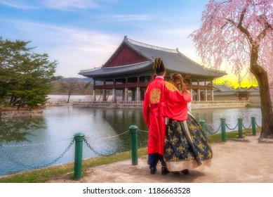 Korean Lover dressed Hanbok traditional of spring cherry blossom in Gyeongbokgung Palace in Seoul, with the name of the palace 'Gyeongbokgung' on a sign South Korea.