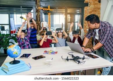 Koreanischer Wissenschaftler mit jungen Schülern mit Laptop- und VR-Headsets während eines Informatik-Unterrichts. Aufgeregte Schulkinder intelligenter, moderner Schulen nutzen virtuelle Realität, um neue Technologien zu erlernen.