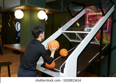 Korean man playing basketball arcade game