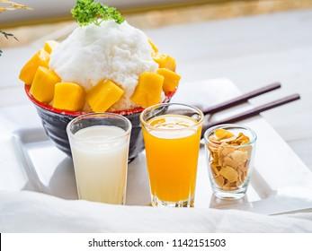 Korean Mango Bingsu, sweet milk dessert Mango taste serve on wood tray and ceramic bowl and Mango syrup, Almond and milk on wood table. Selective focus.