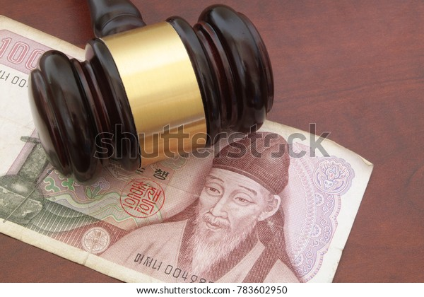 Korean money and wooden gavel on brown table, finance and law concept