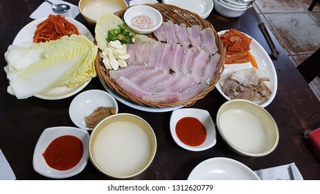 Korean FermentedSkateandSteamedPorkSlicesServedwithKimchi(hongeosamhap), and raw rice wine (makgeolli)