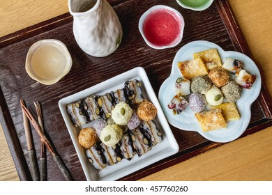 Korean Rice Cake Desserts on a Wooden Tray with Green Tea Water, Glasses, and Wooden Utensils Shot From Above