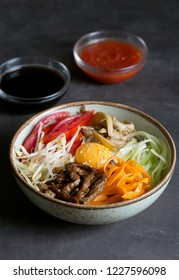 Korean rice dish Bibimbap. Usually served as a bowl of warm white rice topped with vegetables and egg. Black background