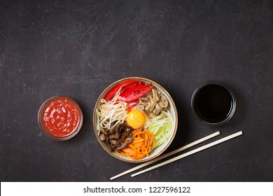 Korean rice dish Bibimbap. Usually served as a bowl of warm white rice topped with vegetables and egg. Black background, top view