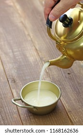 korean rice wine, makgeolli, pouring from a kettle to a cup