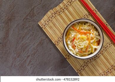 Korean salad of cabbage, carrots, sweet peppers - kimchi in an Asian style on the stone background, selective focus.