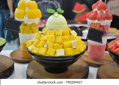 Korean shaved ice cream dessert with sweet toppings, Mango Bingsu or Bingsoo with fresh milk and whipping cream in korea style on black cup.