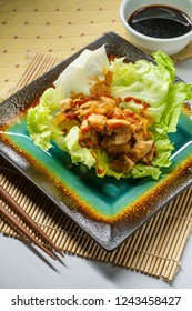 Korean spicy chicken lettuce wrap with gochujang sauce served on bamboo mat