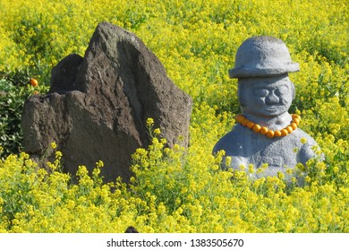 Korean statue is surrounded by yellow flowers.
