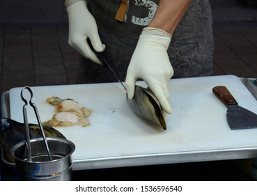 Korean street food, chef shucking and cooking oyster, chef's hand with knife