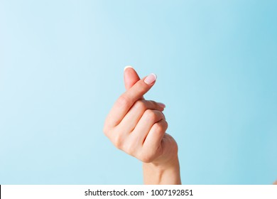 Korean symbol of love with your fingers. A female hand depicts a heart.