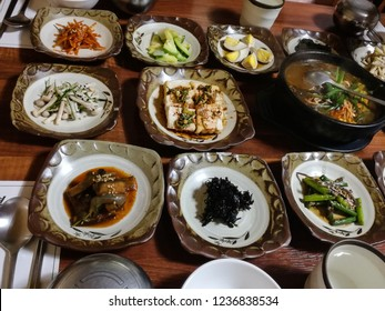 Korean traditional appetizers - tofu, pickled cabbage, green beans, eggplants, mushrooms, laminaria - with hot soup