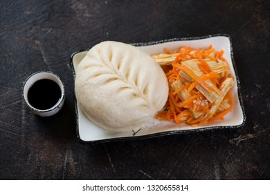 Korean traditional steamed tin-pun with carrot and asparagus salad, high angle view on a dark brown stone background