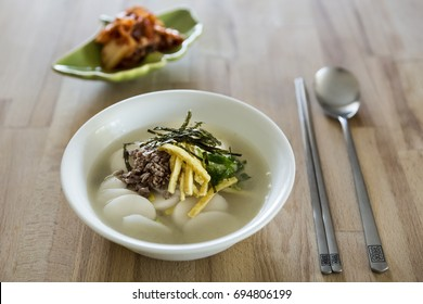 Korean traditional tteokguk or sliced rice cake soup on a wooden table.
