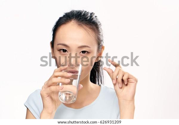 Korean woman drinks pills, tablets in hands